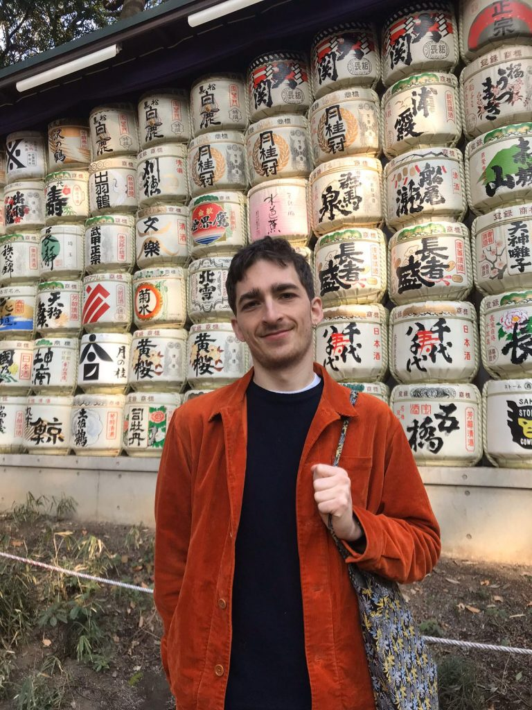Picture of Edward Crowley wearing a orange jacket standing in front of sake barrels